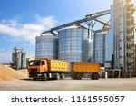 Small photo of Agricultural silo truck of orange color on the territory of grain storage in sunny weather.