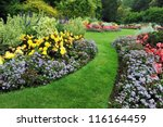 Small photo of Colourful Flowerbeds and Winding Grass Pathway in an Attractive English Formal Garden