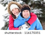 Winter couple happy doing piggyback in winter snow forest. Cheerful smiling young interracial couple having fun outside piggybacking. Asian woman, Caucasian man. - stock photo