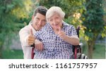 Small photo of Granddaughter, nurse, caring for the elderly, boy(man) hugging grandmother, smiling, happy, walking in the park. Concept: boarding house, sanatorium, a house for the elderly, help for the elderly.