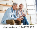 happy elderly couple counting... | Shutterstock . vector #1161762997