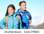 Hikers - hiking couple smiling happy walking cheerful in mountains with backpack. Asian woman hiker with Caucasian man hiker. - stock photo