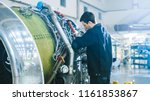 Stock photo aircraft maintenance mechanic inspecting and working on airplane jet engine in hangar 1161853867