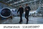 Stock photo team of aircraft maintenance mechanics moving through hangar holding tablet computer 1161853897