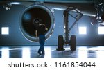 Stock photo in a hangar aircraft maintenance engineer technician mechanic inspects with a flashlight airplane 1161854044