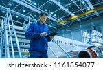 Stock photo aircraft maintenance mechanic in blue uniform is going down the stairs while using tablet in a 1161854077