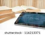 E-learning concept. Digital tablet in study room with image of chalk board on touch screen with handwritten text e-learning. - stock photo