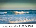 waves in sunset on gold  oast ... | Shutterstock . vector #1162245001