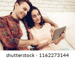a couple watching a tablet on...   Shutterstock . vector #1162273144