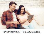 a couple watching a tablet on... | Shutterstock . vector #1162273381