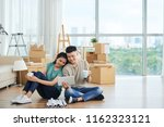 dreamy young couple sitting on... | Shutterstock . vector #1162323121