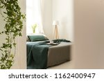 green blanket and pillows on... | Shutterstock . vector #1162400947