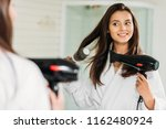happy young woman drying hair... | Shutterstock . vector #1162480924