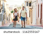 Young happy couple walking holding each others hand in old Spanish town. Stylish man and woman on vacations in Spain, Europe. Tourism and travelling concept.