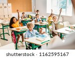 group of pupils raising hands... | Shutterstock . vector #1162595167