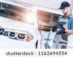 Pre Owned Vehicle Evaluation by Caucasian Car Mechanic. Automotive Concept. - stock photo