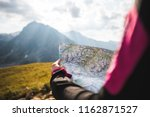 Small photo of Adventurous Girl navigating in with a Topographic Map in the beautiful Mountains of the Austrian Alps