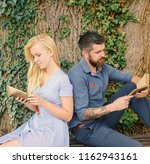 Small photo of Couple in love sit back to back outdoor, nature background. Couple with busy faces reading poems. Romantic couple holds old book with poems about love. Romantic vintage date concept.