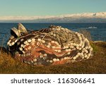 Pile of fishing nets and a reel sitting by the bay in Alaska with a boat going out to sea in fall at the end of the season. - stock photo