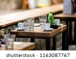 used dishes are on the table in ... | Shutterstock . vector #1163087767