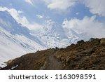 porter trekking among snowy... | Shutterstock . vector #1163098591