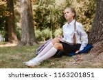 a schoolgirl does lessons in a... | Shutterstock . vector #1163201851