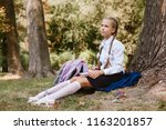 a schoolgirl does lessons in a... | Shutterstock . vector #1163201857