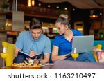 students group eating pizza in... | Shutterstock . vector #1163210497