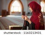 young muslim woman praying in...   Shutterstock . vector #1163213431