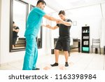 Stock photo young physiotherapist helping athlete to walk between cones in hospital 1163398984
