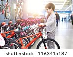 boy chooses a bicycle in a... | Shutterstock . vector #1163415187