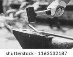 a blacksmith hammering a hot... | Shutterstock . vector #1163532187