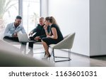 three business people sitting... | Shutterstock . vector #1163601031