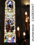 Small photo of stained glass window of a church next to a chandelier