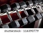 dumbells in a rack at the gym. | Shutterstock . vector #116390779