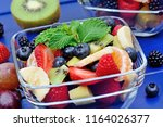 fruit salad in a bowls on blue... | Shutterstock . vector #1164026377