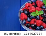 fresh berries in a bowl on table | Shutterstock . vector #1164027334