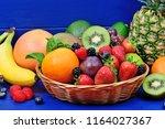 fresh mixed fruits in a basket... | Shutterstock . vector #1164027367