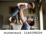 happy dad lifting son up having ... | Shutterstock . vector #1164198334