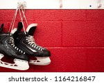 Small photo of Hockey skates hanging in locker room with copy space in red background