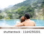 young couple relaxing in hot... | Shutterstock . vector #1164250201