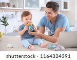 young dad giving water to his... | Shutterstock . vector #1164324391