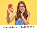 unhappy discontent woman takes... | Shutterstock . vector #1164352597