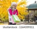 child girl with shopping bags... | Shutterstock . vector #1164359311