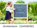 happy little schoolgirl writing ... | Shutterstock . vector #1164360361