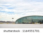 Small photo of hangar with airplane and blue sky. A small plane stands near the hangar and is preparing to take off. Hangar from glass.