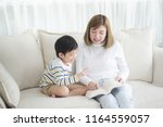asian mother sitting with son... | Shutterstock . vector #1164559057
