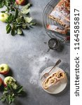 Small photo of Homemade sliced puff pastry apple strudel pie on cooling rack served with ripe fresh apples, branches, fork and sugar powder over grey texture background. Flat lay, space