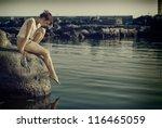 Young sad woman on the rocks - stock photo