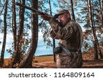 a hunter with a hunting gun and ... | Shutterstock . vector #1164809164